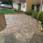 Tumbled block paved driveway with retaining sleeper walls