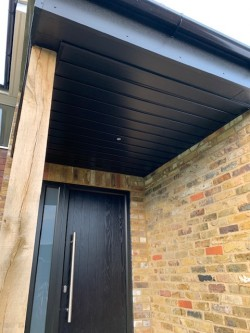 Overhang porch incorporating an oak post on a brick pier and black UPVC wood grained effect cladding , fascias & soffits