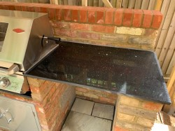 Brick built bespoke BBQ constructed from original stock brick , incorporating grill , fridge , granite worktops , lighting & electrical points . The housing is a solid oak frame with pitched clay tile roof , guttering , downpipes & shiplap cladding .