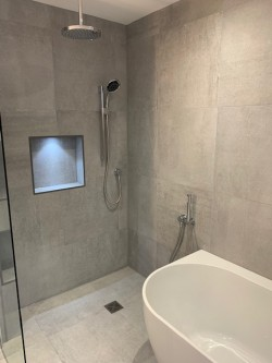 Fully tiled wet room incorporating recessed boxings , L.E.D lighting , wireless bath & shower controls & free standing feature bath
