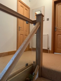 Standard softwood staircase with over clad oak veneer & 6mm toughened glass balustrading with chrome glass clamps